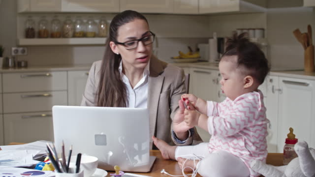 Woman working from home and caring for baby video