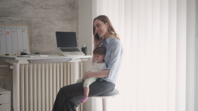 4K: Woman working in home office with her baby video