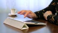 Woman working on digital tablet, drinking coffee video