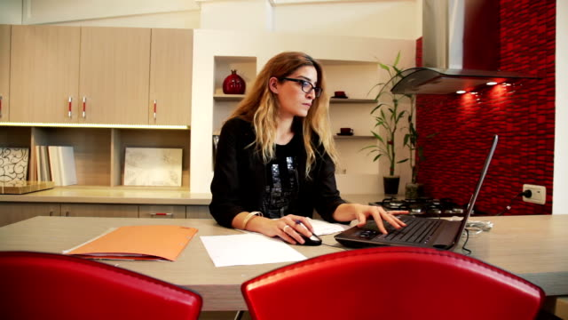 Woman working on laptop in the kitchen video