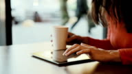 Woman working on tablet at cafe and drink coffee video