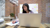 Woman working online at a creative office video