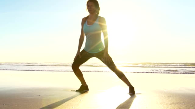 Woman Working out on Beach at Sunset. Stretching. Fitness. Tying Shoes, Active Lifestyle. Slow Motion video