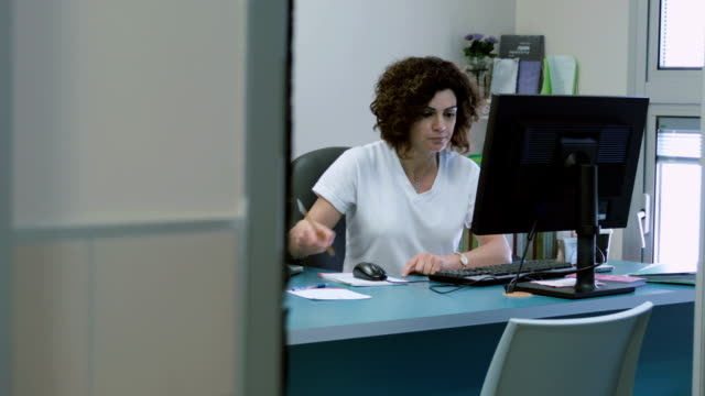 Woman works at the computer making notes and calculations video