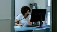 Woman works at the computer talking on the phone video