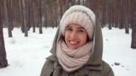Woman wrapped in a winter scarf posing at the camera on a wintry day video