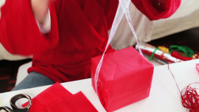 Woman wrapping a Christmas gift video