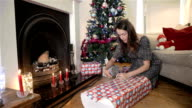 Woman wrapping a large Christmas present video