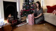 Woman wrapping Christmas Presents by the tree video