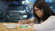 Woman writing in notebook at coffee cafe with coffee , cake and smartphone , 4k(UHD) video