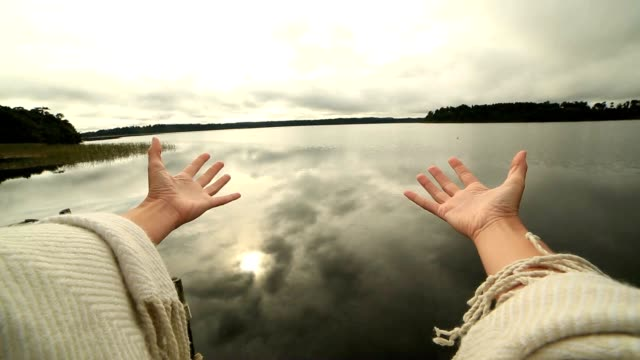 Woman's arms stretch towards mountain lake, success concept video