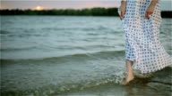 Woman's bare feet in the water of the lake. video
