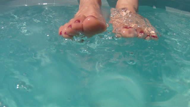 Woman's feet splashing in water video