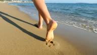 Woman's feet walking by the sea video