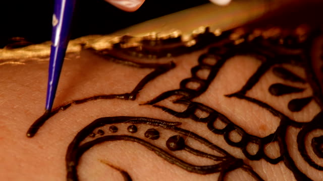 Woman`s hand being decorated with henna tattoo, mehendi, on black, close up, cam moves top down video
