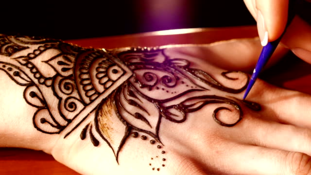 Woman`s hand being decorated with henna tattoo, mehendi, on black video