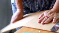 Woman's hand clapping at down with a piece of acrylic sheet at the edge of a table and snap it in a quick push down motion. video