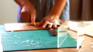 Woman's hand cutting pattern on acrylic sheet with Plastic Cutting Tools. video