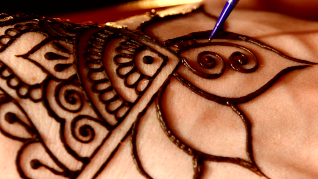 Woman`s hand decorated with henna tattoo, mehendi, on black, close up, cam moves top down video