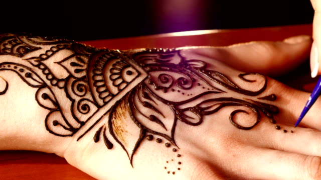 Woman`s hand decorated with mehendi, on black background video