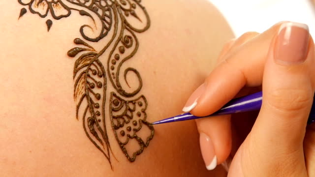 Woman`s hand decorated with mehendi, on white, close up, cam moves top down, slow motion video