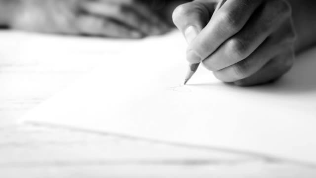 A woman's hand drawing something inspirationally with a graphite pencil video