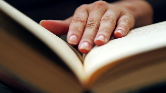 Woman's hand holds a book and moves fingers along page while reading video