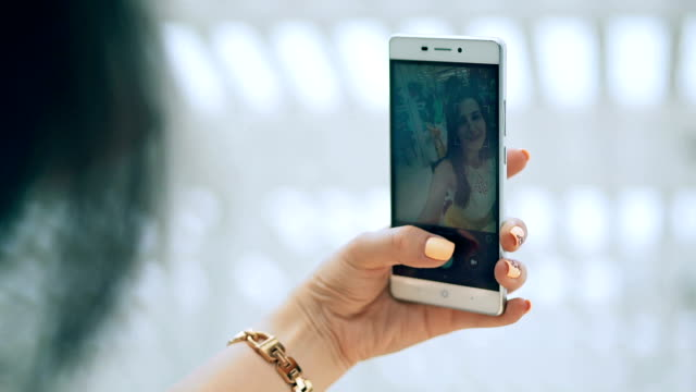 woman's hand making selfie using smartphone in cafe. smarphone closeup video