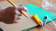 Woman's hand measuring ruler master skin for acrylic sheet and cutting pattern on acrylic sheet with Plastic Cutting Tools. video