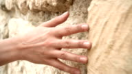 Woman's hand moving over old stone wall. Sliding along. Sensual touching. Hard stone surface video