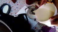 woman's hand poured tea with milk from a bucket in a thermos top view video