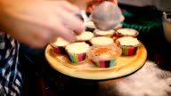 Woman's hand sprinkling icing sugar over fresh muffins. video