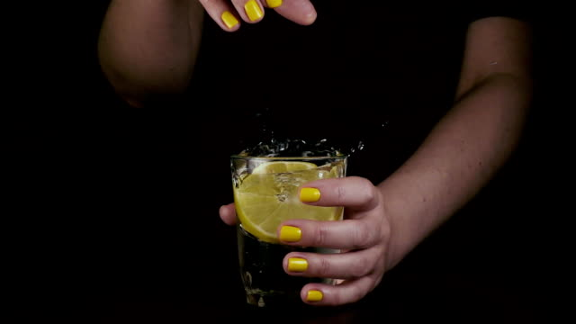 A woman's hand throws a lemon into a glass. Slow motion video