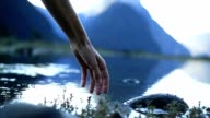 Woman's hand touches lake surface video