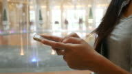 woman's hand using smart phone with fountain background video