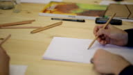 Woman's hand with pencil draws on paper sheet in line video