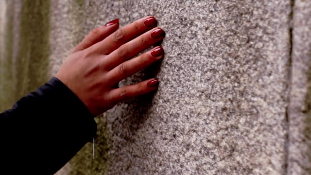 Woman's hand with red nails touching concrete wall video