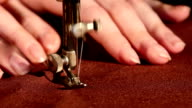 Woman's hands behind her sewing process on brown tissue video