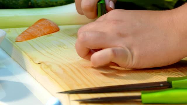 Woman's hands cut into carrots video