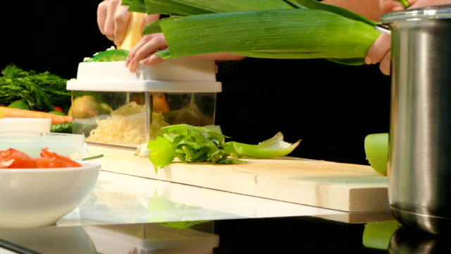 Woman's hands cut the leeks and chop the cheese video