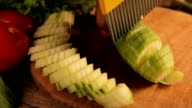 Woman's hands cutting cucumber, behind fresh vegetables video