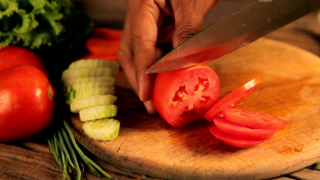 Woman's hands cutting tomato, behind fresh vegetables. video