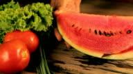 Woman's hands cutting watermelon, behind fresh vegetables video