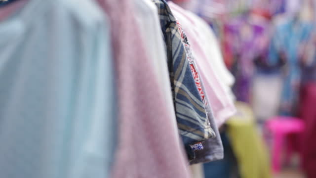 Woman's hands looking through t-shirts rack video