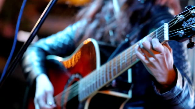 Woman's hands playing acoustic guitar on concert video