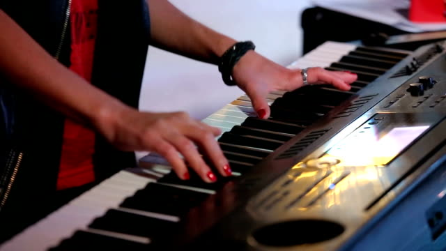 Womans hands playing keyboard on concert video