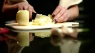 Woman's hands slicing cutting onion on the kitchen counter video