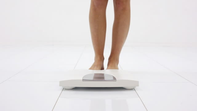 Woman's legs on the white scale. video