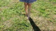 Woman's legs walking in the grass video