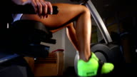 woman's muscular legs on bicycle training machine, closeup video